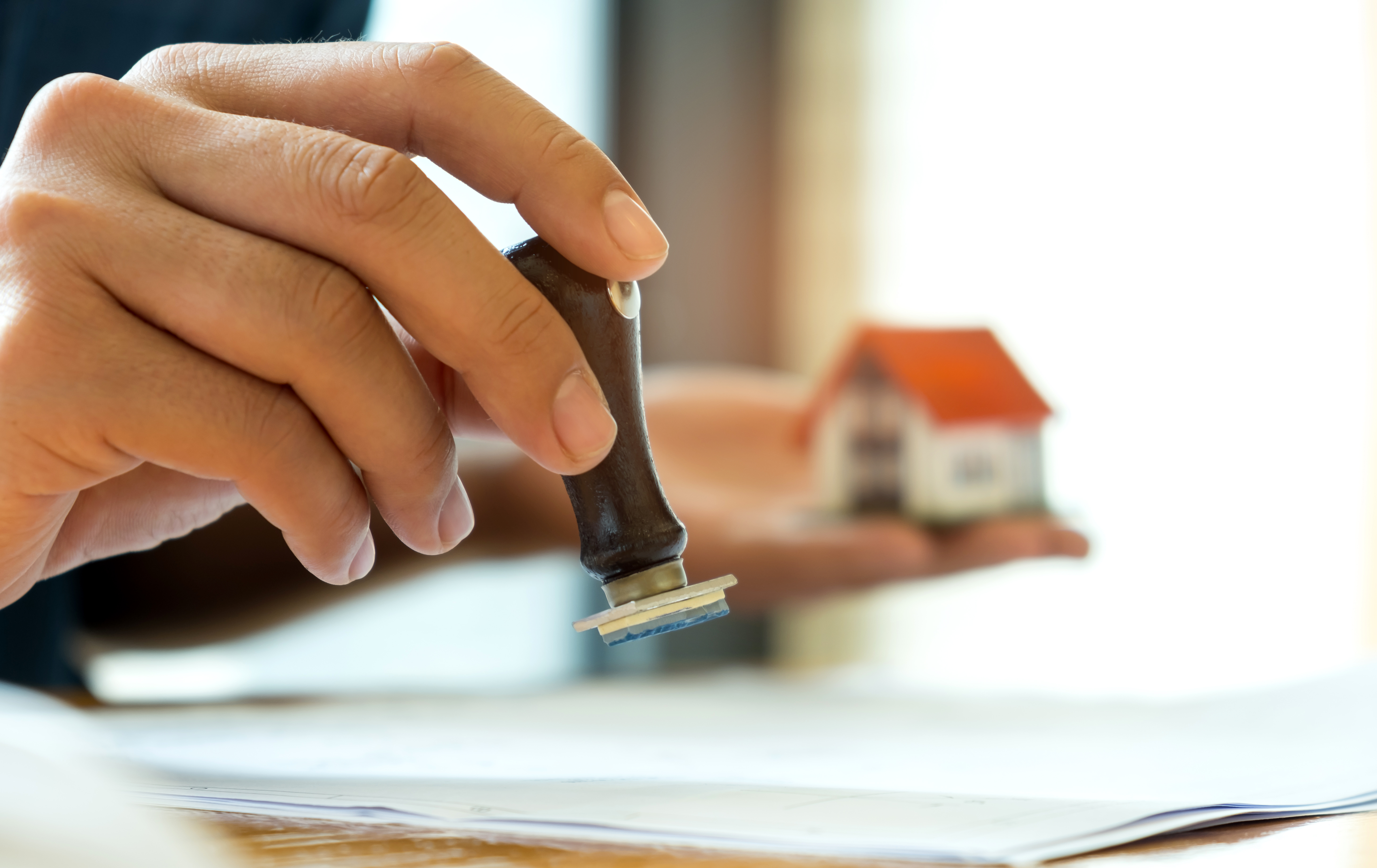 close-up-rubber-stamp-and-model-house-in-hand-P7PRWV3